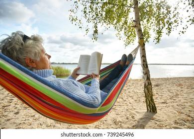 happy elderly woman enjoying in hammock at the beach, sunny autumn day