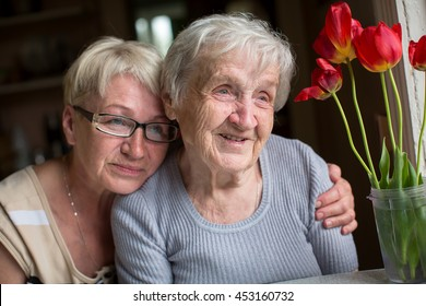 Happy elderly woman with her daughter in behind an embrace.