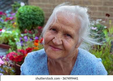 Happy elderly woman in her flower garden