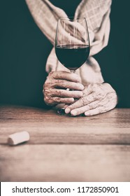 Happy elderly woman holding red wine glass on her wrinkle hands.Concept of daily glass of wine improves memory of people over the age of 60.Healthy concept or older wine is better,the older the better