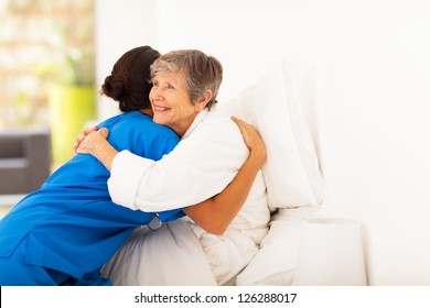 happy elderly woman hugging caregiver on bed