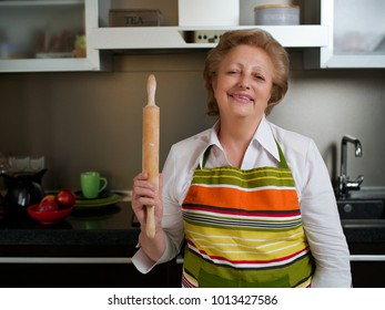 Happy elderly woman in the kitchen holding cooked dumplings and showing thumbs up.