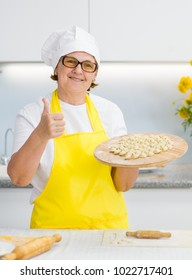 Happy elderly woman in the kitchen holding cooked dumplings and showing thumbs up