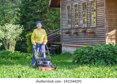 Happy elderly woman mows the lawn with an electric lawn mower on allotment near her wooden country house in a warm sunny day.. Garden work