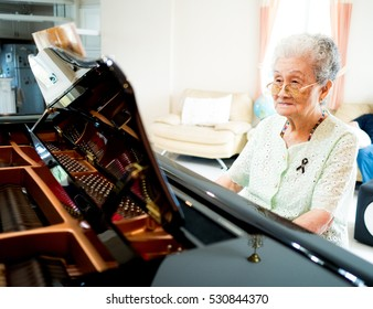 Happy elderly woman pianist playing piano at home. Retirement woman relaxed by learning to play piano.