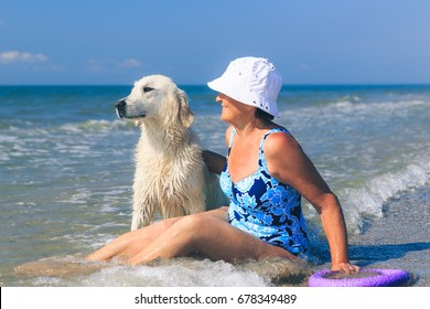 Happy elderly woman playing with her golden retriever on the sea coastline at morning