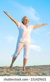 Happy elderly woman raised her hands at a beach