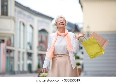 Happy elderly woman with shopping bags