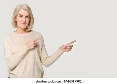 Happy elderly woman showing to empty space for copyspace. Smiling old female point by fingers to the right, attract attention to blank place. Lady in years studio portrait isolated on grey background