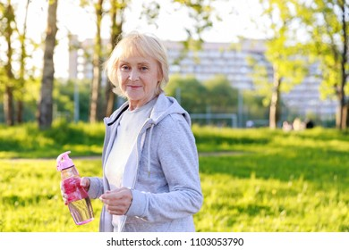 Happy elderly woman in sportswear in a sunny park. Be active and energetic until old age, longevity, biohacking