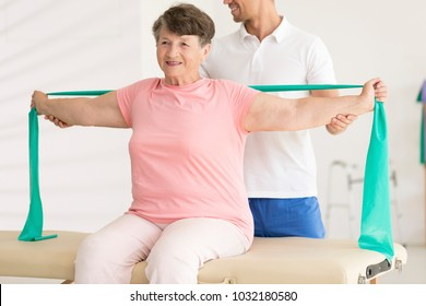 Happy elderly woman stretching with elastic tape during physiotherapy