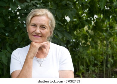 happy elderly woman in a summer park
