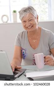 Happy elderly woman using laptop computer, smiling, drinking tea.