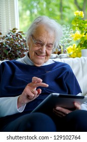 Happy Elderly woman using a tablet and laughing