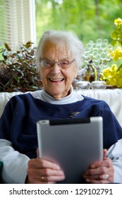 Happy Elderly woman using a tablet looking at the camera and laughing
