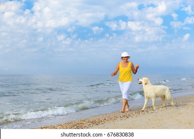 Happy elderly woman walking along a beach with her golden retriever at the morning
