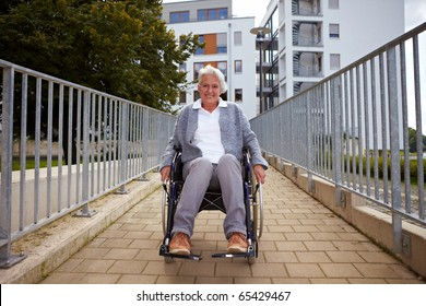 Happy elderly woman in wheelchair using a ramp