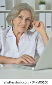 happy Elderly woman working on laptop in office