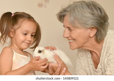 happy elderly woman and a young girl with a small rabbit