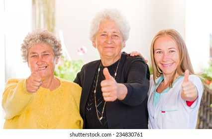 Happy elderly women with their carer showing thumbs up