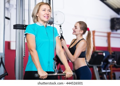 Happy elderly and young women doing powerlifting on machines in jym
