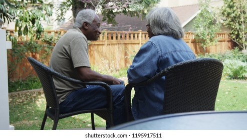 Happy eldery black couple talking in the backyard