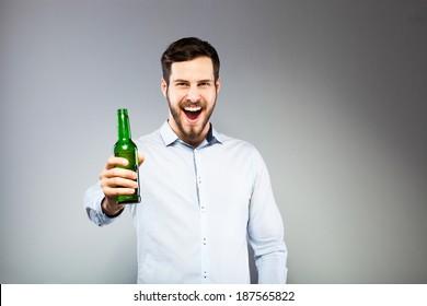 happy elegant man drinking beer, on grey background