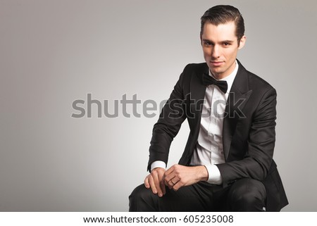 57520711efcf happy elegant man in tuxedo and bowtie is sitting and smiling on grey  background