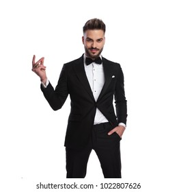 happy elegant man in tuxedo snapping his fingers on white background