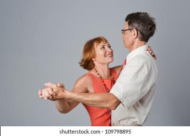 Happy elegant senior couple is dancing.