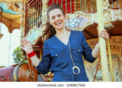 happy elegant woman in blue jeans overall riding on the carousel and waving.