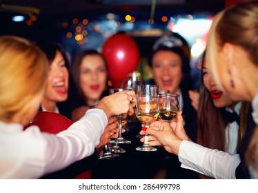 happy elegant women clinking glasses in limousine, focus on glasses