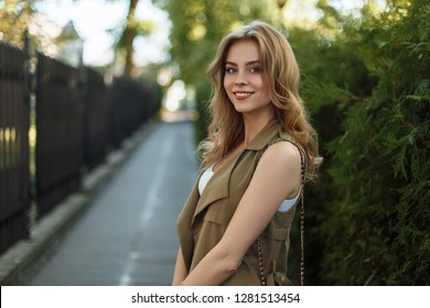 Happy elegant young woman in trendy summer dress with stylish black leather handbag posing on the street near green trees and an old iron fence. Beautiful girl with a wonderful smile.