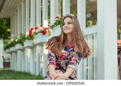 Happy elegant young woman in trendy summer floral dress posing near wooden white fence with red flowers. Beautiful girl with a wonderful smile looking to side thoughtful daydreaming. Mixed race, Asian