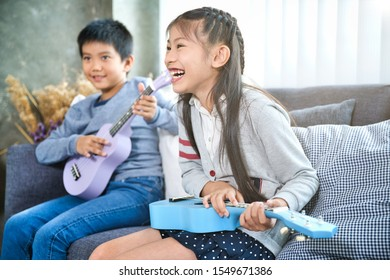Happy elementary age Asian little kid is smiling  while playing a ukulele during a private music learning lesson at home