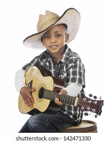 A happy elementary cowboy strumming a guitar while sitting on an old barrel.  On a white background.