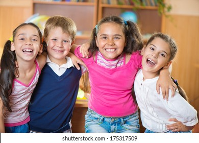 Happy elementary students in classroom at school