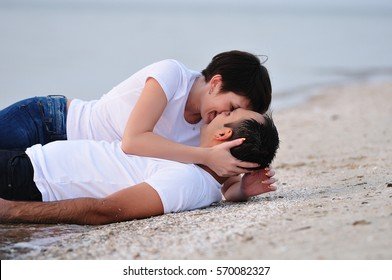 Happy embracing young couple lie on sand of beach with  sea on background