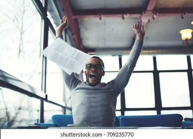 Happy emotional afro american student celebrating passing examination throwing up in air notings with information, excited dark skinned businessman celebrating completing work on startup project