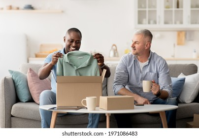 Happy emotional clients looking in box, surprised by gift at home. Smiling middle aged african american guy pulls out clothes of purchases, senior man with cup of drink looks at him in living room