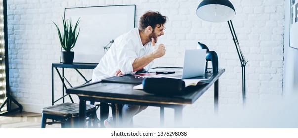 Happy emotional hipster guy laughing at online content checking via laptop computer during job in coworking office with modern interior, cheerful male freelancer carefree smiling at joke from message