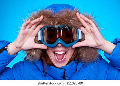 happy emotional woman in ski glasses and winter coat over blue background