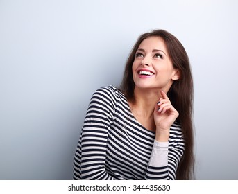 Happy emotional woman thinking and looking up with toothy smiling on blue background