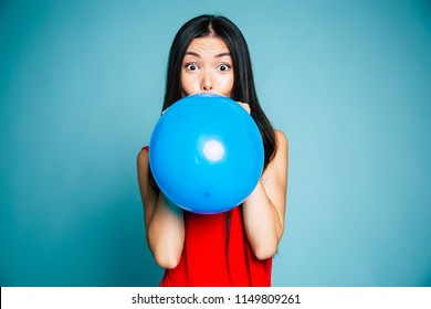 Happy emotional young asian woman in red is blowing a blue balloon in studio. Portrait of beautiful chinese girl. Shopping concept