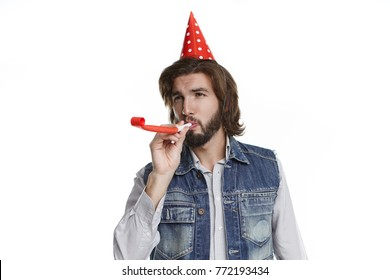 Happy emotional young bearded man blowing party horn, congratulating friend on his birthday, being glad to celebrate such festive occasion. Party, fun, joy, celebration and entertainment concept