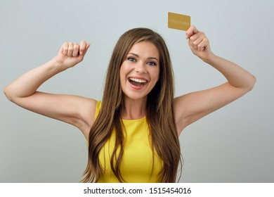 Happy emotional young woman holding credit card. Isolated female portrait.