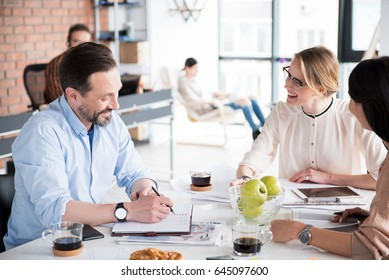 Happy employee is looking at male coworker with sincere laugh. They sitting around table in office. He writing in notebook