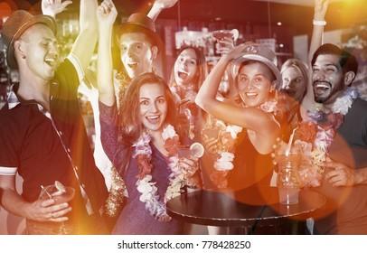 Happy employees are having fun on the hawaiian party.