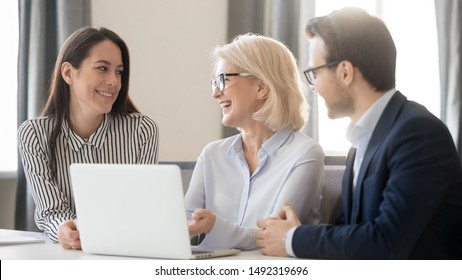Happy employees interns discussing new corporate software, having fun, pleasant conversation, using laptop, mature coach mentor training staff, explaining online project, horizontal photo