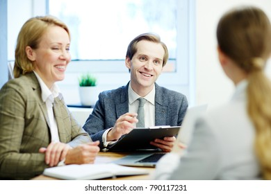 Happy employers having talk with one of applicants during interview